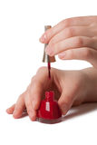 Applying red nail polish on female fingers Stock Photo