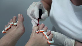 Applying red nail polish on toes. In a sterile environment stock footage