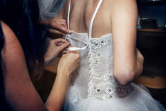 Applying ribbon to the corset Stock Images