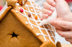 Applying royal icing on gingerbread house. With a posh Royalty Free Stock Image