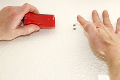Applying Spackling. Close up of male hand about to apply white spackling paste to two holes in the wall while holding on other hand a red tool to smooth Stock Photography