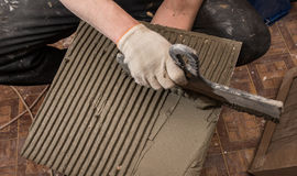 Applying a special solution on the tile laying it on the floor o Stock Image