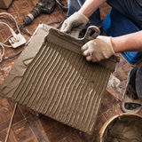 Applying a special solution on the tile laying it on the floor o Stock Photo