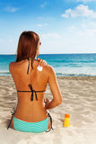 Applying sun protection on tanned skin. Back of gorgeous young woman applying sun protection on tanned skin sitting on sandy beach Royalty Free Stock Image