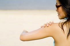 Applying Suncream At Beach Stock Photo