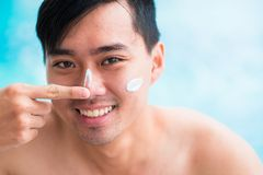 Applying sunscreen. Handsome man applying sunscreen on his face Stock Photo