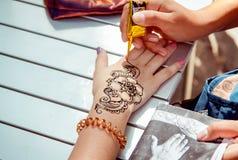 Applying temporary henna tattoo Stock Image