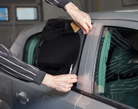 Applying tinting foil on a car window Royalty Free Stock Photography
