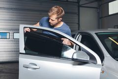 Applying tinting foil onto a car window. In a workshop royalty free stock photography