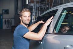 Applying tinting foil onto a car window Stock Image