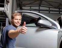 Applying tinting foil onto a car window Stock Photos
