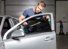 Applying tinting foil onto a car window Royalty Free Stock Photo