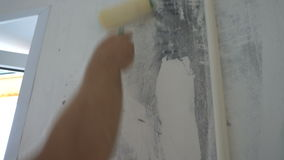 Applying wallpaper paste to the wall with a roller, preparation for wallpapering.  stock video footage