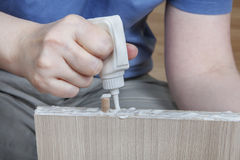 Applying wood glue, carpenter gluing wooden parts for furniture, Royalty Free Stock Photography