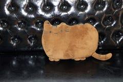 Appoggi la forma del gatto nel colore marrone sul sofà di cuoio nero il cuscino è una borsa del panno farcita con le piume fotografie stock