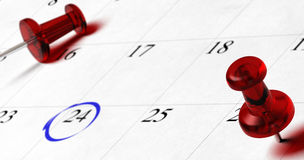 Appointment. Agenda with red pupins pointing on different dates with blur effect, number 24 is surounded by a blue circle Royalty Free Stock Photography