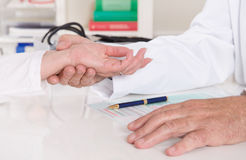 Appointment at doctor: measure pulse with fingers. Royalty Free Stock Image
