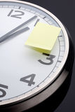 Appointment reminder. Clock with yellow sticky note Royalty Free Stock Photos