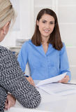 Appointment at a specialist for finance: female customer and adv. Iser sitting at desk talking about a contract or business solutions.Concept teamwork or job royalty free stock photography
