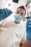 Apport de la vie à votre sourire Le jeune dentiste masculin regarde des dents au-dessus de la bouche du patient ouvert À l'intéri photo stock