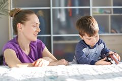 Apport et enfants concept Le tir horizontal de la mère assez jeune dans le T-shirt occasionnel pourpre, prend soin de son petit f image stock
