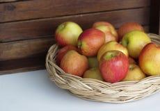 Appples rouges dans le panier sur la table blanche, fond en bois, fruits images stock