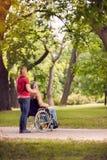 Apprécier l'homme supérieur dans le fauteuil roulant et la fille en parc Image libre de droits