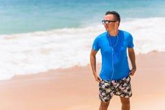 Apprécier la musique folâtre le jeune homme heureux de mode de vie dans des écouteurs marchant sur le bord de mer Images stock