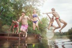 Apprécier la partie de rivière avec des amis Groupe des beaux jeunes heureux à la rivière ensemble photos stock
