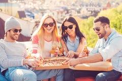 Apprécier la pizza avec des amis Photo libre de droits