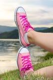 Apprécier par le lac Femme utilisant les espadrilles roses Photos libres de droits