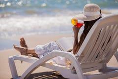 Apprécier une boisson par la plage Image libre de droits
