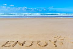 Appréciez l'inscription sur le sable humide de plage sous le dessin du soleil et le Se photos libres de droits