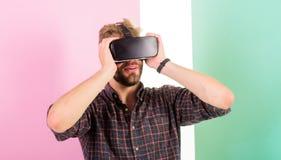Appréciez la réalité virtuelle Équipez le type non rasé avec des verres de VR, fond rose Technologies modernes d'utilisation de h photos stock