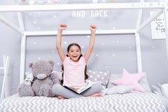 Appréciez le concept La fille heureuse ont plaisir à rester dans le lit Le petit enfant avec les mains augmentées apprécient le l photo libre de droits