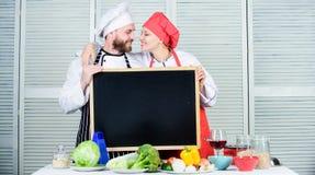 Appréciez le déploiement d'amusement dans la cuisine Cuisinier principal et cuisinier de préparation étreignant en faisant cuire  image libre de droits
