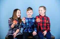 Appréciez le goût de la droite de consommation enfants en bonne sant? Peu enfants tenant les pommes rouges Petit groupe de consom photo libre de droits