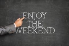 Appréciez le texte de week-end sur le tableau noir avec le pointage de main d'homme d'affaires photos stock