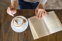 Appréciez un jour gratuit avec le livre et la tasse de cappuccino image stock