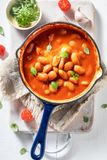 Appréciez vos haricots cuits au four a fait des tomates et des herbes fraîches images libres de droits