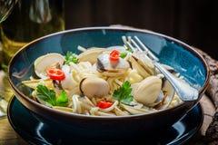 Appréciez vos pâtes de fruits de mer avec les palourdes, le persil et les poivrons images stock