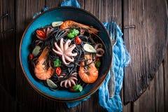 Appréciez vos pâtes de noir de fruits de mer avec la crevette, le poulpe et le persil images libres de droits