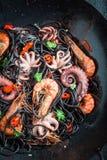 Appréciez vos pâtes de noir de fruits de mer faites de poulpe, crevettes roses de tigre images stock