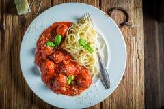 Appréciez vos spaghetti Bolonais avec les boulettes de viande et le parmesan photographie stock libre de droits