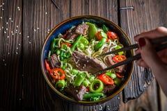 Appréciez votre nouille asiatique dans la cuvette foncée avec des baguettes photographie stock libre de droits