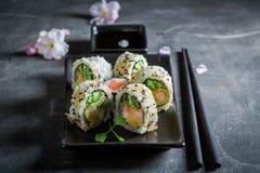 Appréciez votre préparation de sushi faite de saumons et avocat image libre de droits