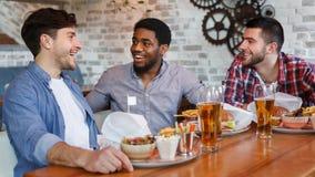 Appr?cier la bi?re avec des amis Hommes s'asseyant dans la barre ensemble images stock