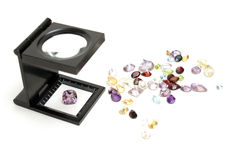 Appraisal of Gemstones. A loupe with various cut gemstones for the jeweler to inspect their quality and value stock photography