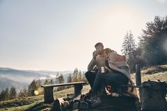 Appreciating every minute together. Beautiful young couple having morning coffee while sitting by the campfire in mountains