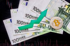 Appreciation of virtual money bitcoin. Green arrow and silver Bitcoin on hundred euro bills and paper forex chart index rating on. Exchange market background stock photography